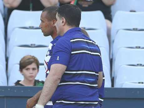 Moses Mbye of the Bulldogs is assisted from the field.