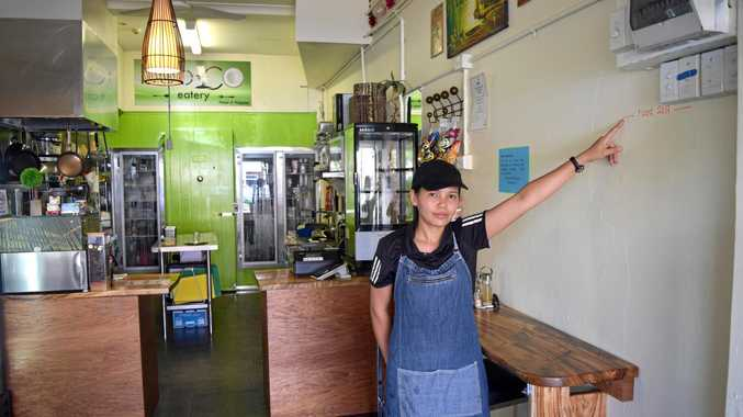 Marmonie Altman pointing to the flood level in her shop BooCo, which refers to bamboo and coconuts.
