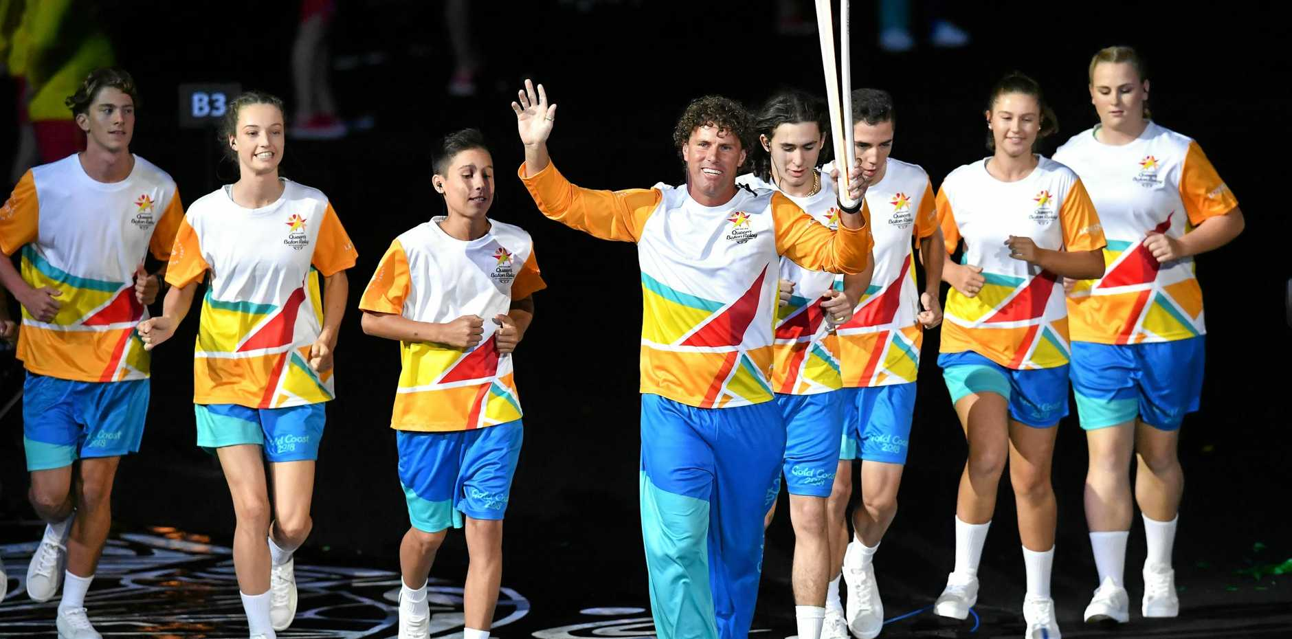 Former Hockey player Brent Livermore (centre) enters the stadium with the Queen's Baton during the Opening Ceremony of the XXI Commonwealth Games at Carrara Stadium on the Gold Coast, Australia, Wednesday, April 4, 2018.