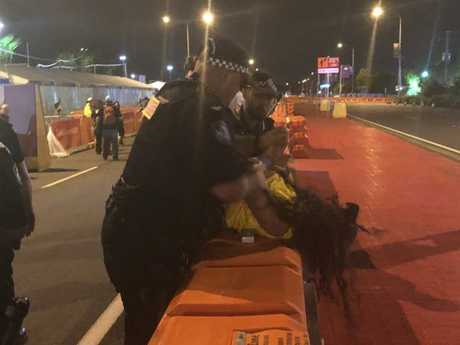 Demonstrators were held down after allegedly trying to storm the Gold Coast stadium after a day of peaceful protests turned ugly, with scuffles breaking out. Picture: Britt Ramsey