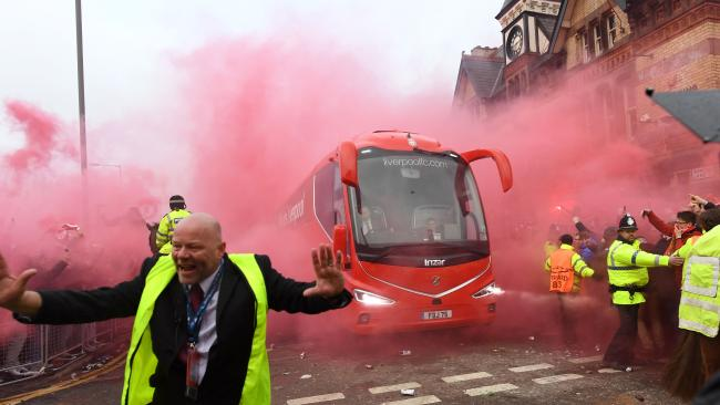 Police hold back supporters as Liverpool players arrive by bus.