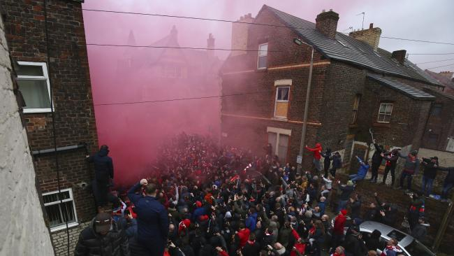 A flare burns as football fans try to see the Manchester City team bus