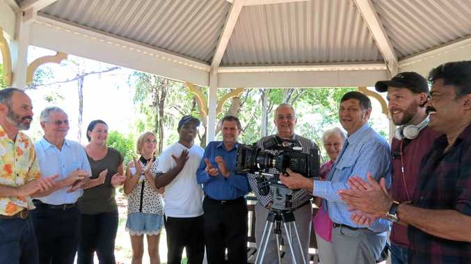 ON A ROLL: Banana Shire Mayor Nev Ferrier turns on the camera to signify the start of filming. He is surrounded by the cast, councillors and director Joy K. Mathew (far right).