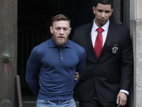 Ultimate fighting star Conor McGregor, left, is led by an official to an unmarked vehicle in Brooklyn.  Picture:  AP