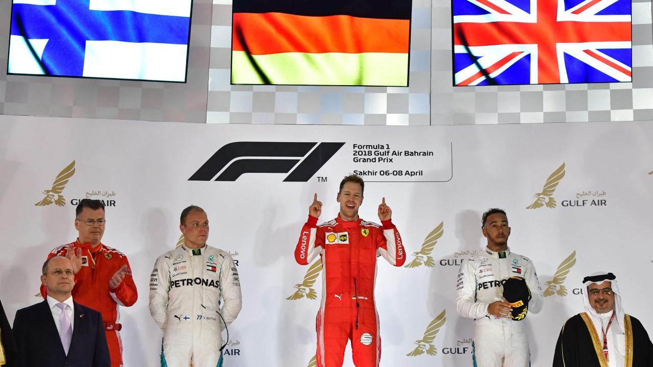 Ferrari's German driver Sebastian Vettel (C) celebrates on the podium after winning the Bahrain Formula One Grand Prix with Mercedes' Finnish driver Valtteri Bottas (L) who came second and Mercedes' British driver Lewis Hamilton (R) who came third.