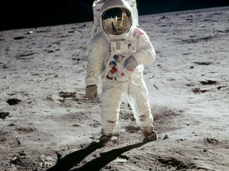 Buzz Aldrin walks on the lunar surface in 1969, his plexiglass helmet reflecting Neil Armstrong taking his picture. Picture: NASA