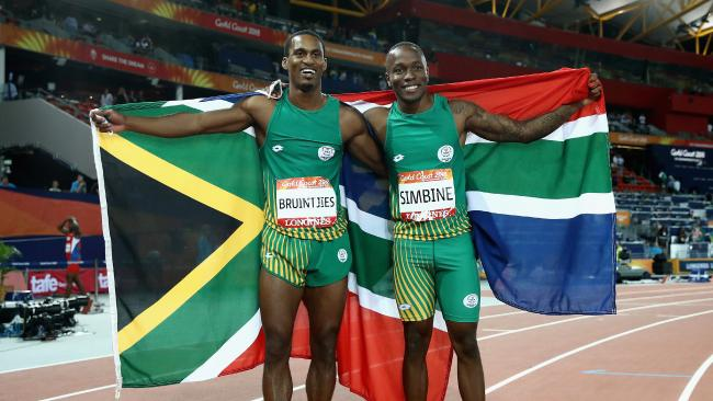 Akani Simbine celebrates winning gold with silver medalist Henricho Bruintjies.
