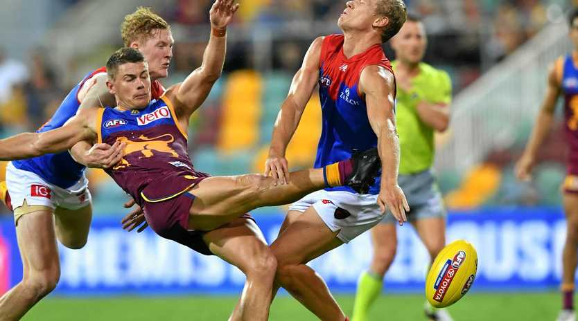 Dayne Zorko of the Lions (centre) kicks the ball under pressure during between the Brisbane Lions and the Melbourne Demons at the Gabba in Brisbane.