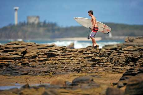 A surfer checks out the improving surf conditions at The Bluff, Alex Headland.