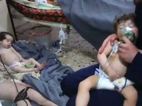 An unidentified volunteer holds an oxygen mask over a child's face at a hospital fin Douma.
