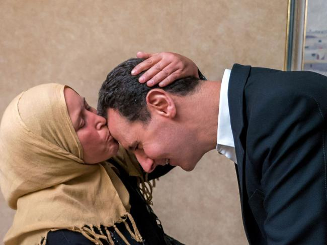 A handout picture released by the official Facebook page of the Syrian Presidency on April 10 shows Syrian President Bashar al-Assad being kissed by a woman whose relative is believed to be captured by opposition fighters in Douma.