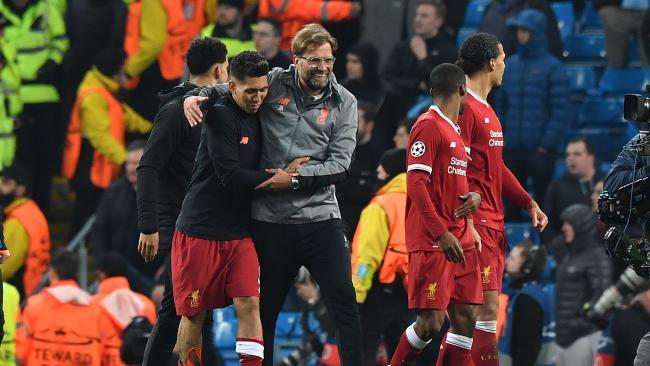 Liverpool's German manager Jurgen Klopp congratulates Liverpool's Brazilian midfielder Roberto Firmino