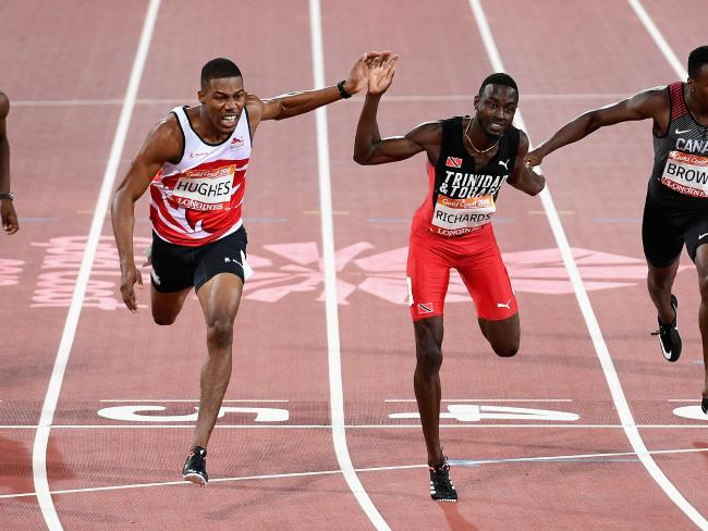 Zharnel Hughes of England crosses the line to win gold ahead of Jereem Richards of Trinidad and Tobago