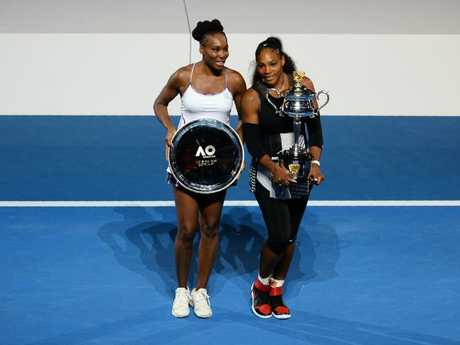 Serena Williams holds the winner's trophy as she poses with runner up Venus at the Australian Open in 2017. Pic: AFP PHOTO / Greg Wood.