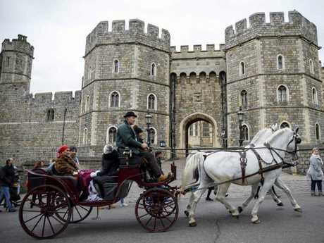 Tourists ride in a horse-drawn carriage past the main entrance of Windsor Castle, where Prince Harry and Meghan will marry in May. Picture: AFP