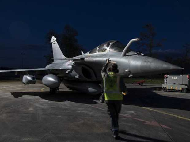 A crewman directs a Dassault Rafale fighter aircraft before taking off from Saint Dizier air base, eastern France, for an air strike in Syria. Picture: French Defense Ministry/ECPAD via AP
