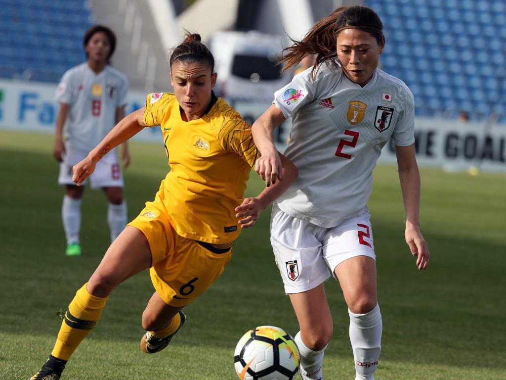 Australia's midfielder Chloe Logarzo (L) controls the ball ahead of Japan's defender Utsugi Rumi.