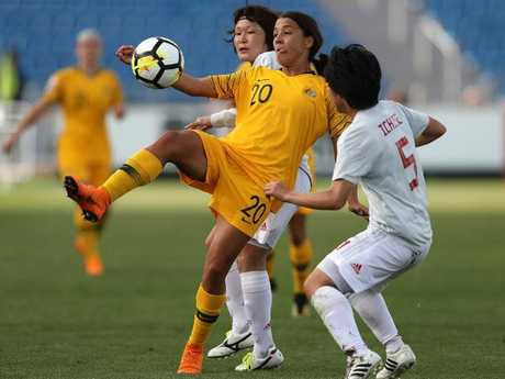 Samantha May Kerr of Australia kicks the ball under pressure from Muzuho Sakaguchi (L) and Nana Ichise (R) of Japan during the AFC Women's Asian Cup Group B match between Japan and Australia.