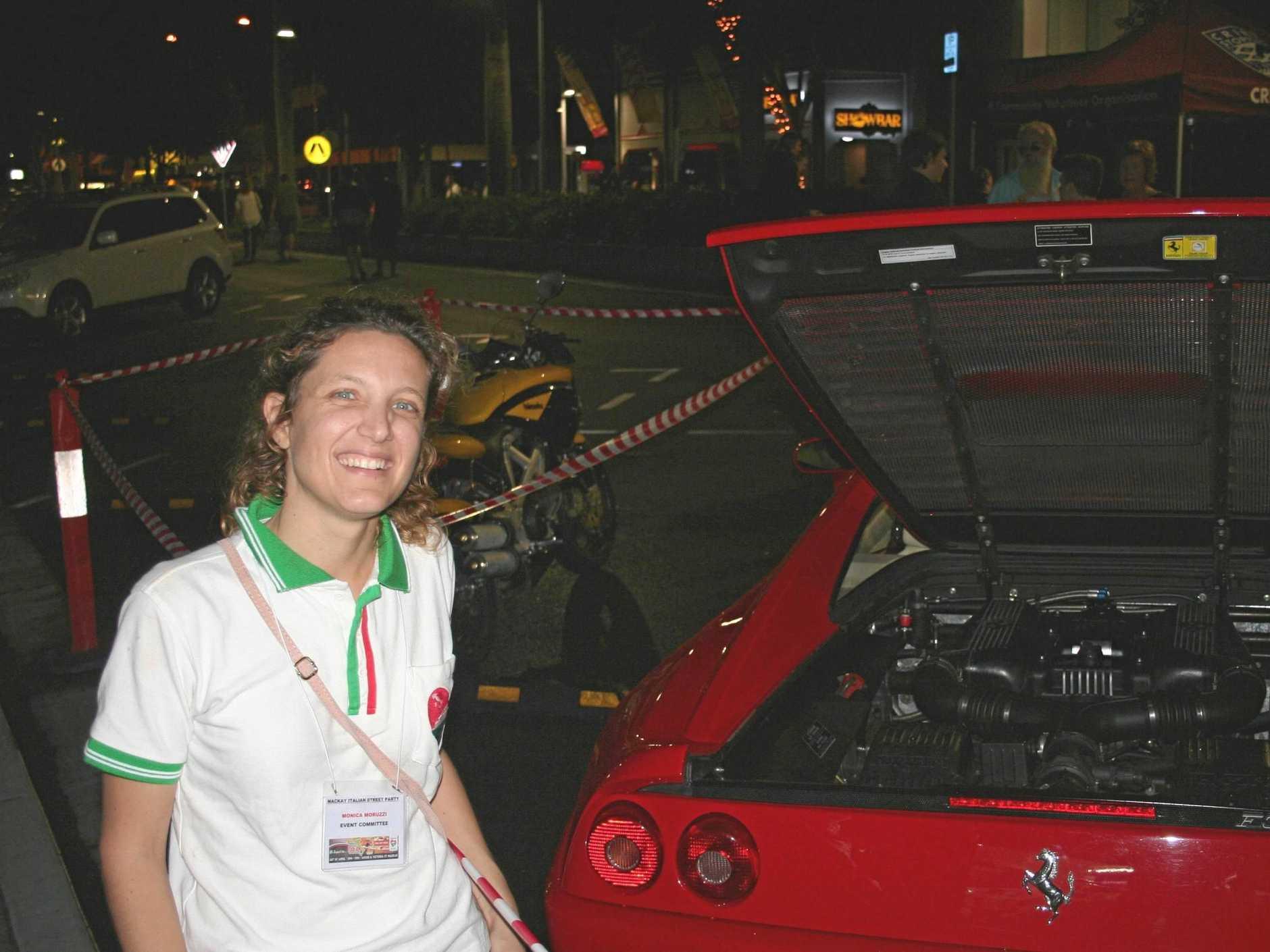 MKY150418 Monica Moruzzi from the Mackay and Districts Italian Association posing next to a Ferrari F355 Berlinetta at the Mackay Italian Street Party on April 14 2018