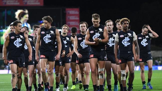 Carlton players leave the field after the horror loss to North Melbourne.