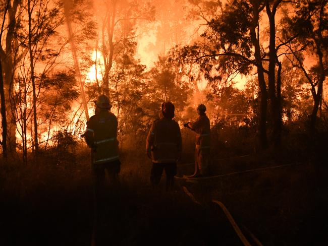 Firefighters battle flames close to homes at Wattle Grove. Picture: AAP/Brendan Esposito