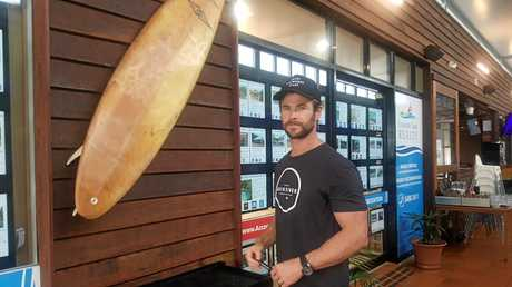 Keen surfer Chris Hemsworth signs a surfboard outside Rainbow beach cafe Coffee Rocks at Rainbow on Monday morning.