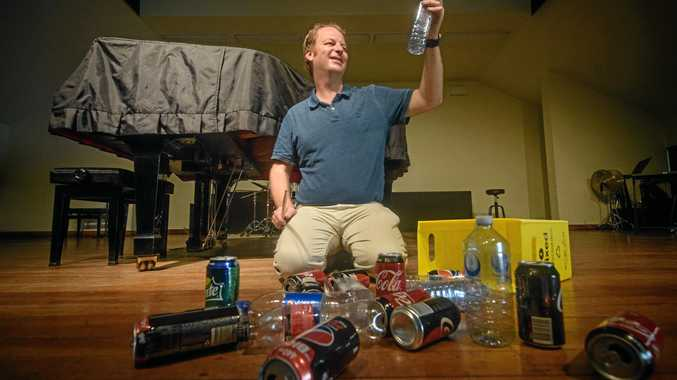 DUAL CAUSE: Clarence Valley Conservatorium director Adam Wills with some of the cans and bottles that can help raise funds for future musicians.