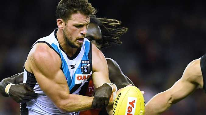 Power captain Travis Boak gets wrapped up by Anthony McDonald-Tipungwuti in the loss to Essendon on Sunday. Picture: Mark Brake/Getty Images