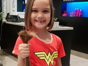 Young girl cuts hair for a cause