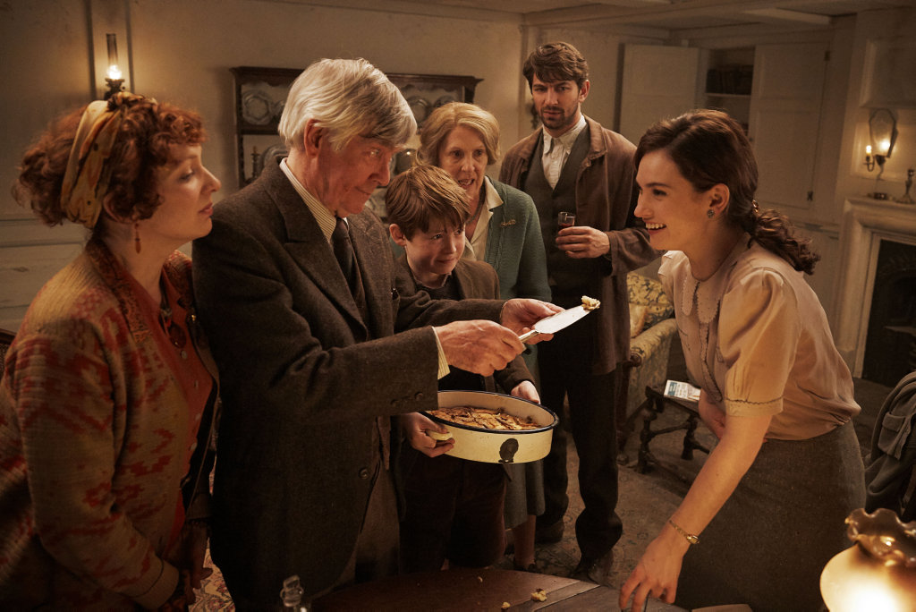 Tom Courtenay, Penelope Wilton, Katherine Parkinson, Kit Connor, Michiel Huisman and Lily James in a scene from them movie The Guernsey Literary and Potato Peel Pie Society.