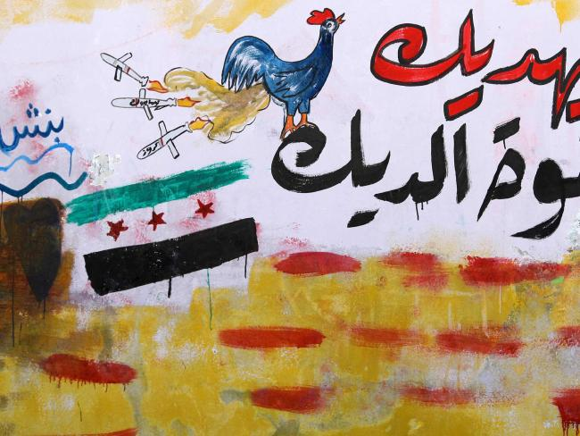 Graffiti in the rebel-held Syrian town of Binnish compares the President's strike to 'a rooster's fart.' Picture: AFP Photo/Omar Haj Kadour