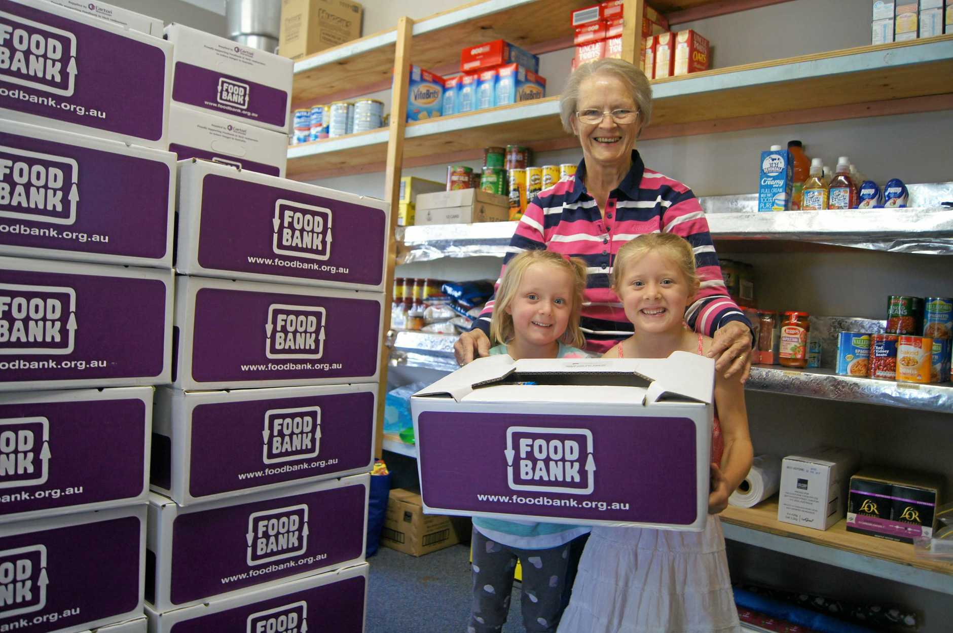 HELPING HAND: Sisters Makenzie and Allie help distribute Foodbank hampers that could help one of their friends.