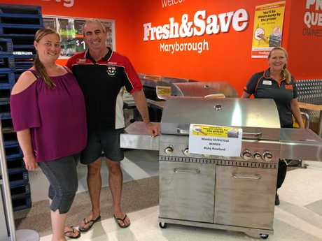 Ricky Rowland and Anastasia Smith accept their prize from Fresh & Save store manager Belinda Dukes (right) after winning one of 14 barbecues for the store's first birthday competition.