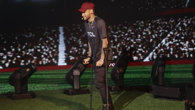 Brazil's soccer star Neymar walks on crutches during a promotional event