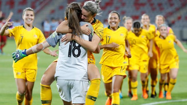 Alanna Kennedy hugs teammate Mackenzie Arnold.