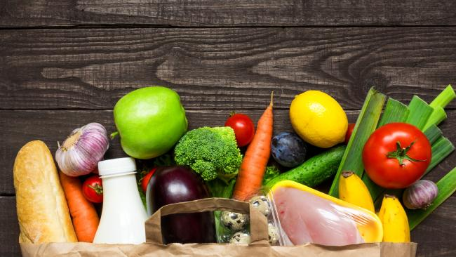 News Corp Australia's 2017 Win Groceries for a Year worth $25,000 Competition — stock image. Full paper bag of different health food on rustic wooden background. Top view. Flat lay