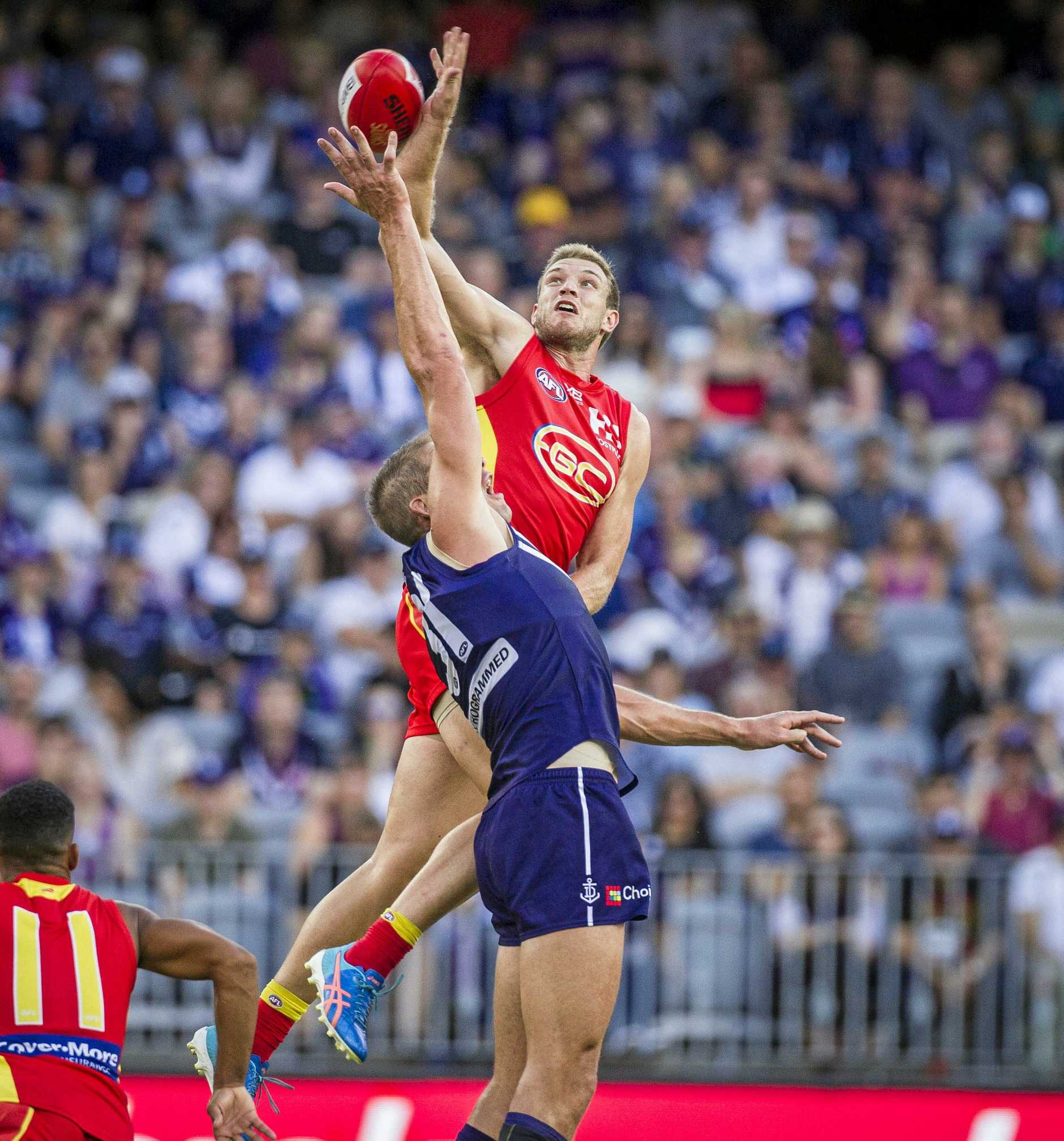 Gold Cost big man Sam Day outjumps Fremantle's Aaron Sandilands in a ruck contest in their round three clash in Perth.