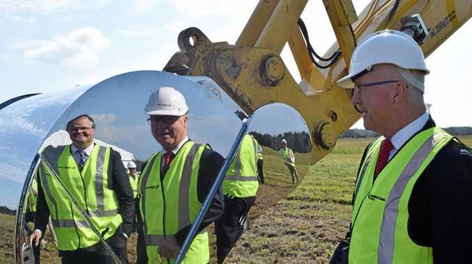 Sunshine Coast Mayor Mark Jamieson inspects a shiny excavator bucket at a ceremony to mark the start of construction on the new Sunshine Coast Airport runway.