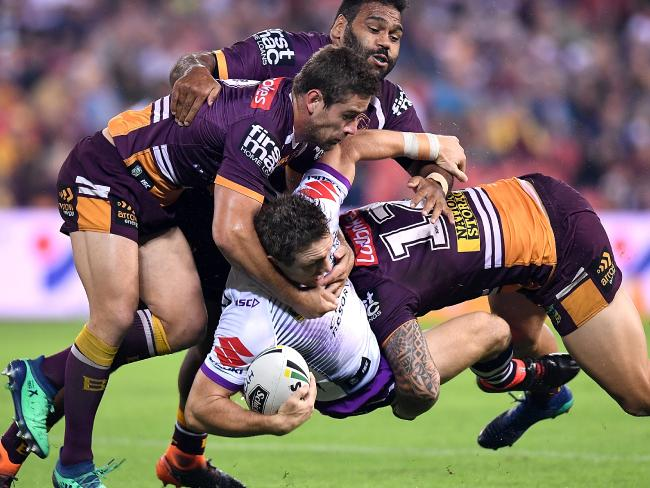 Ryan Hoffman is tackled by the Broncos defence.