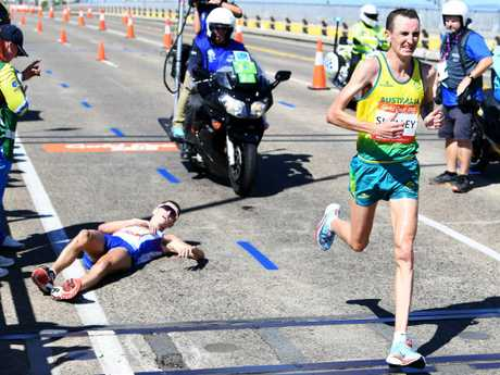 Michael Shelley (R) passes Callum Hawkins (L) after he collapsed less than 2km from the finish line. Shelley won the gold in the Marathon final. Picture: AAP Image/Tracey Nearmy