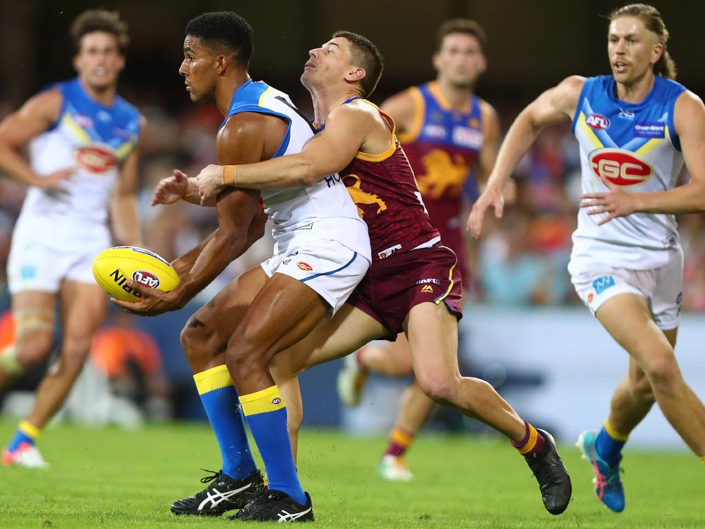 Touk Miller is tackled by Dayne Zorko. (Photo by Chris Hyde/Getty Images)