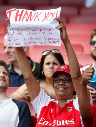 A fan holds up a sign thanking Arsenal's French manager Arsene Wenger