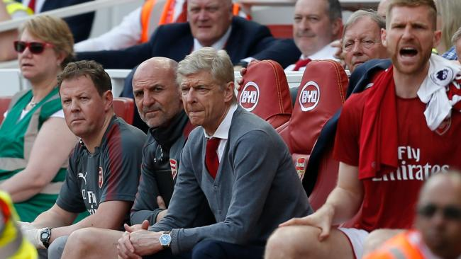 Arsenal's French manager Arsene Wenger (C) watches on from his seat