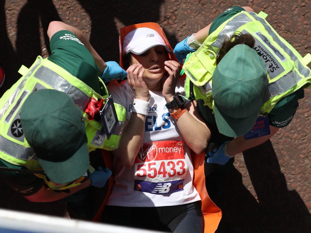 Paramedics assist a runner. / AFP PHOTO / Daniel LEAL-OLIVAS