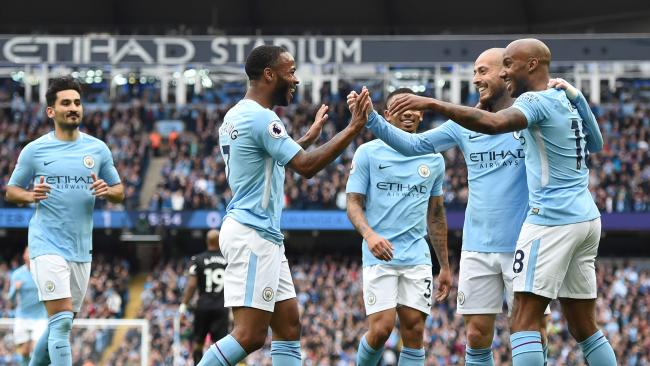 Manchester City's English midfielder Raheem Sterling (C) celebrates scoring their second goal with teammates