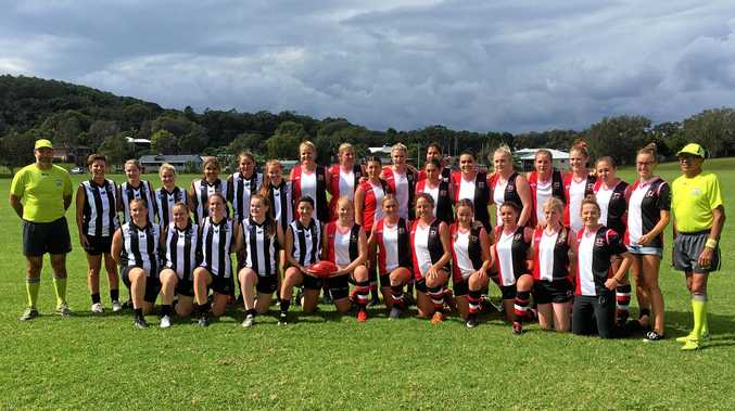 The players from Port Macquarie and Sawtell/Toormina line up for an historic photo prior to the first AFL North Coast women's match being played on Saturday.