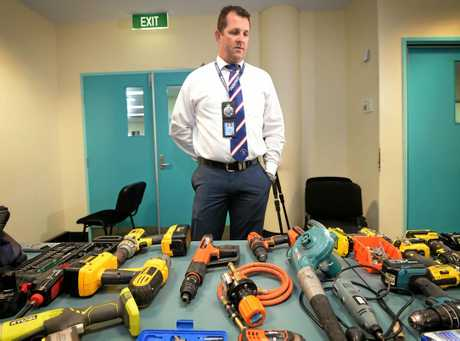 Detective Senior Sergeant Luke Peachey looks over a range of suspected stolen property found at a Campbell Street address by the police while executing a warrant.