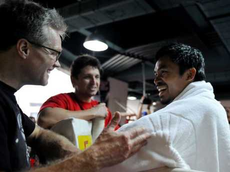 Manny Pacquiao shares a lighter moment with Freddie Roach (L).