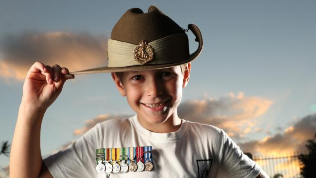 Noah MacKinney-Clohesy, 7, with his father's medals and slouch hat. Picture: Liam Kidston