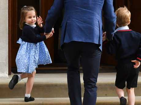 Princess Charlotte turns to wave at the media as she and her brother Prince George are led into the hospital by their father. Picture: AFP Photo / Ben Stansall